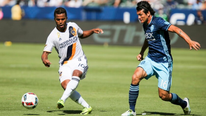 Galaxy midfielder Giovani dos Santos, left, moves the ball away from Seattle forward Nelson Valdez during a game on Sept. 25.