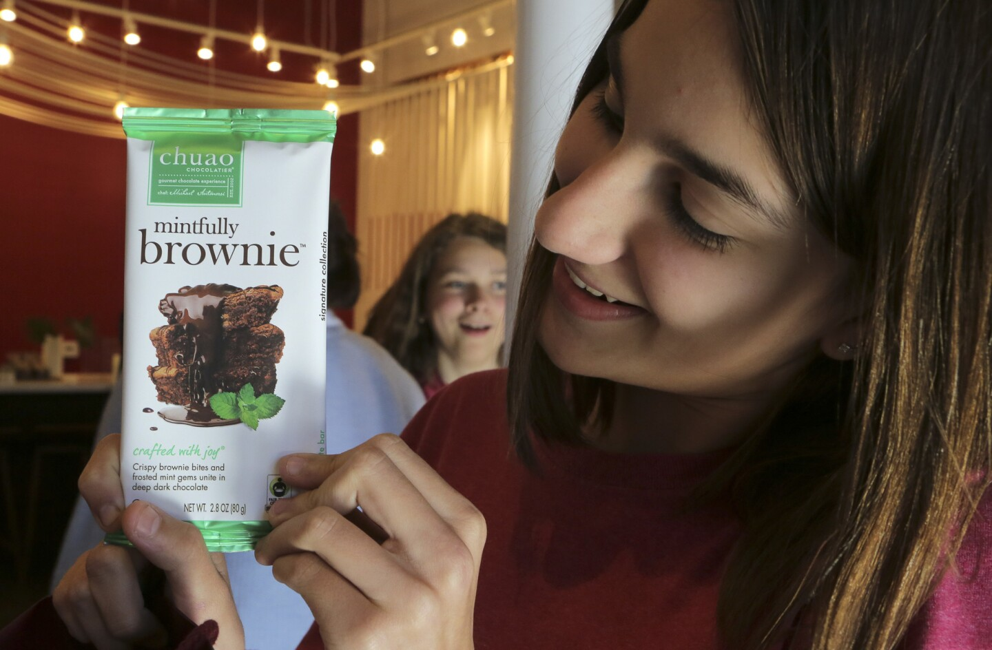Vista Christian School seventh-grader Karlee Mejia shows off a Mintfully Brownie Bar during its unveiling at Chuao Chocolatier headquarters in Carlsbad on Wednesday. Her science class helped provide inspiration for the bar's ingredients as part of a class project last spring.