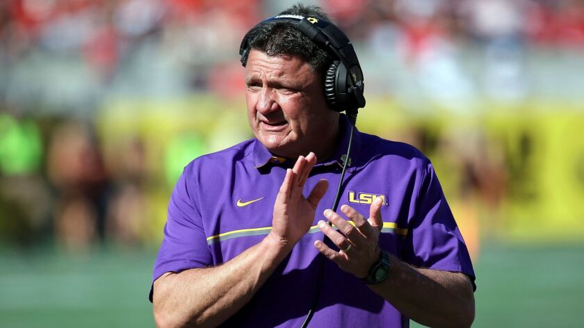 LSU coach Ed Orgeron claps while standing on the sideline.