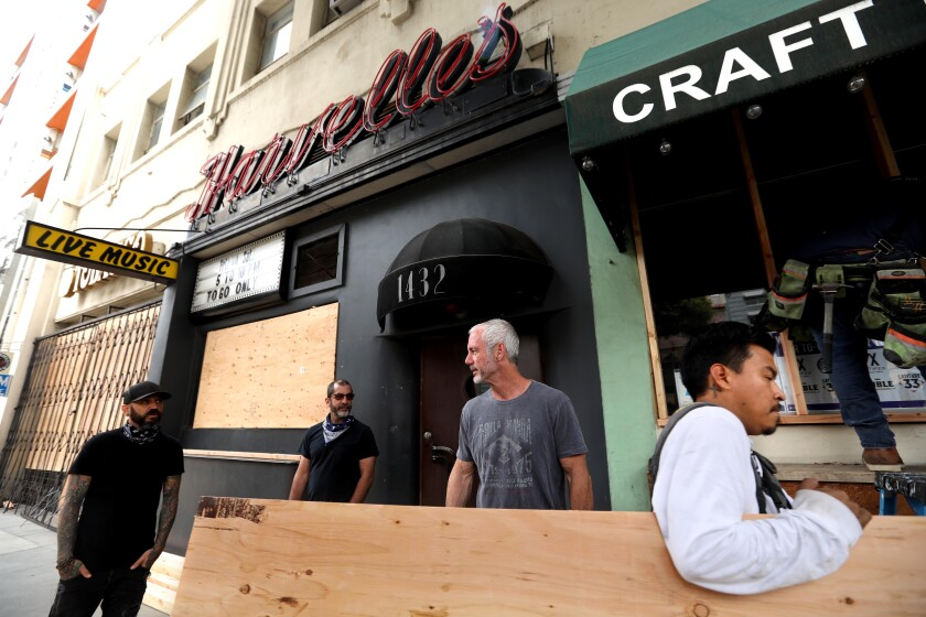 Jason Gochin, from left, Damian Anastasio and Cevin Clark, co-owners of Harvelle's, stand in front of their place in Santa Monica.