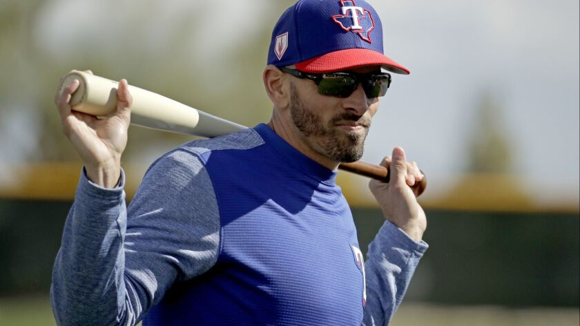Texas Rangers manager Chris Woodward watches a drill during spring training baseball practice Monday