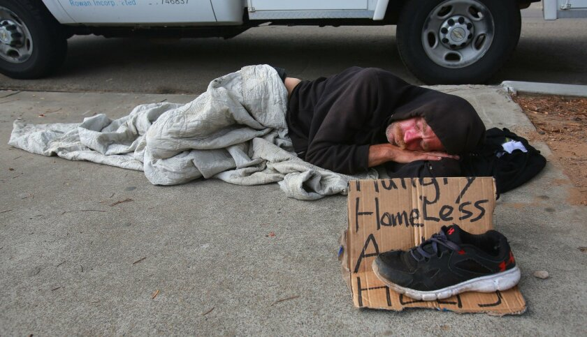 A man named Jerry sleeps on a downtown San Diego sidewalk on Aug. 10, 2016. Officials report a sharp increase in the homeless population living outdoors, halfway through the city's three-year plan to reduce their numbers.
