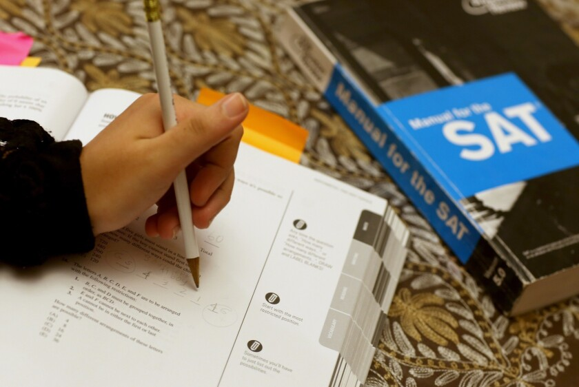 A student works on practice questions from an SAT prep book.