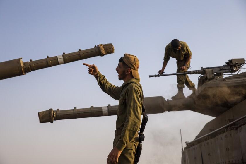 Soldados israelíes trabajan en tanques en la región controlada por Israel de los Altos del Golán, cerca de la frontera con Siria y de la frontera con Líbano, el martes 28 de julio de 2020. (AP Foto/Ariel Schalit)
