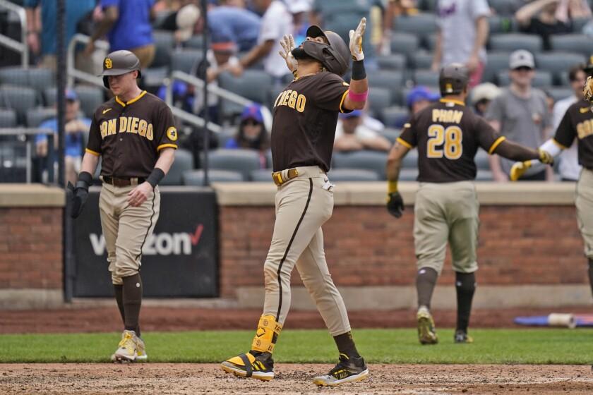 Fernando Tatis Jr. (centro) de los Padres de San Diego reacciona tras batear un grand slam