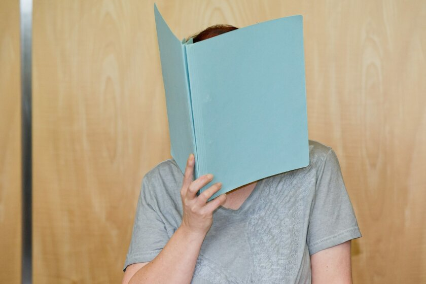 Defendant Andrea G. ,  who is accused of murder, covering her face with a folder, in the court room of the regional court in Coburg, Germany, Tuesday July 12,  2016. A couple have gone on trial in Germany after the remains of eight babies were found at their apartment in Bavaria last year. The 45-y