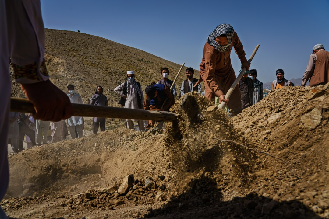 People wait as others dig a grave with shovels.