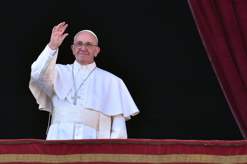 """Pope Francis waves from the balcony of St. Peter's basilica during the traditional """"Urbi et Orbi"""" Christmas Day message at St. Peter's square in the Vatican."""