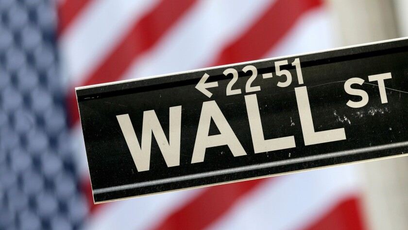A Wall Street sign is framed by a U.S. flag hanging on the facade of the New York Stock Exchange.