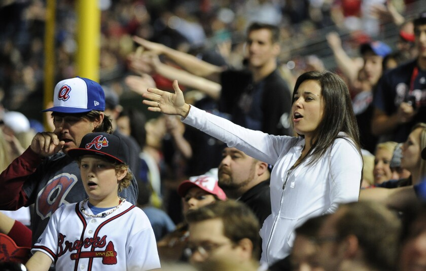 "FILE - In this May 2, 2014, file photo, Atlanta Braves fans do the tomahawk chop during the ninth inning of a baseball game with the San Francisco Giants, in Atlanta. The Atlanta Braves say they have no plans to follow the lead of the NFL's Washington Redskins and change their team name. The team said in a letter to season ticket holders they are examining the fan experience, including the tomahawk chop chant, and have formed a ""cultural working relationship"" with the Eastern Band of the Cherokees in North Carolina. (AP Photo/David Tulis, File)"