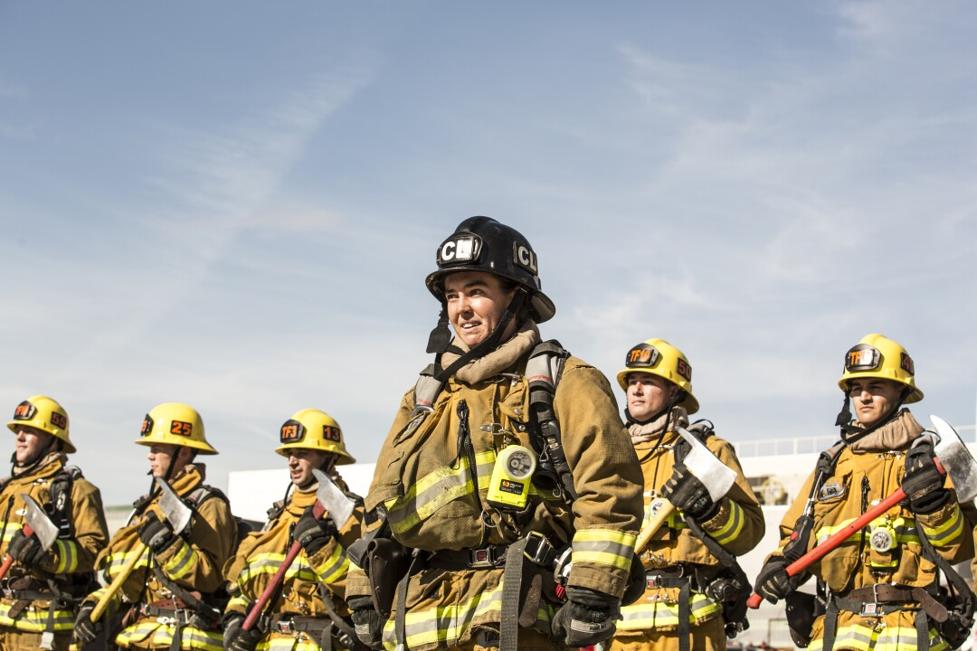 A woman in a firefighters hat with the letters CL stands in front of a line of other firefighters carrying axes.