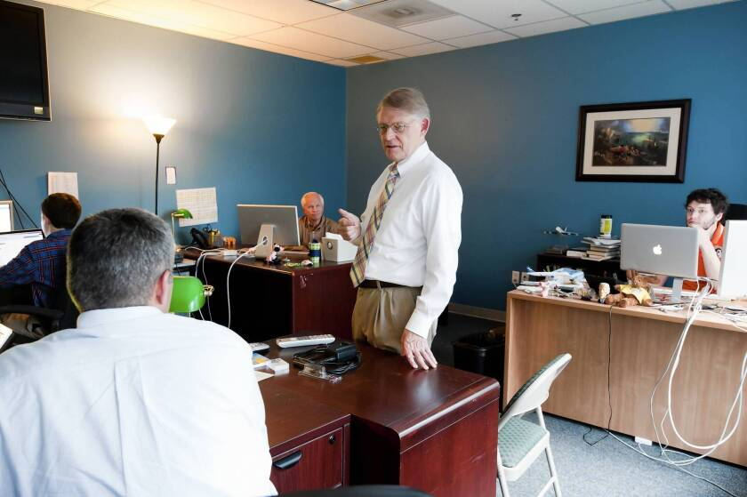 Roy H. Beck, president of the anti-immigration reform group NumbersUSA, speaks with staff members in the group's offices in Arlington, Va.