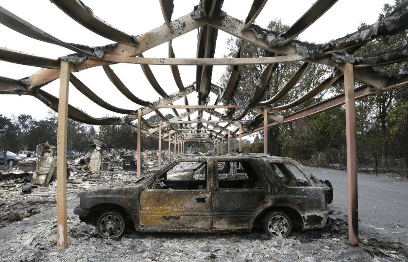 The charred metal skeleton of a carport and vehicles at the Middletown Manor apartments in Middleton, Calif. Nearly all the 1,000 citizens of the town were forced to evacuate the Valley fire.