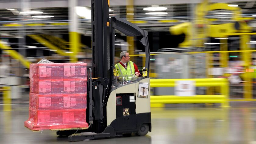 FILE - In this Feb. 13, 2015, file photo, a forklift operator moves a pallet of goods at an Amazon.c