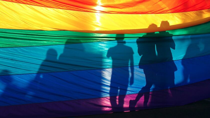 Supporters of same-sex marriage take their photo in front of a rainbow flag on University Ave. in Hillcrest after the U.S. Supreme Court ruling cleared the way for same-sex marriage in California on Wednesday, June 26, 2013.