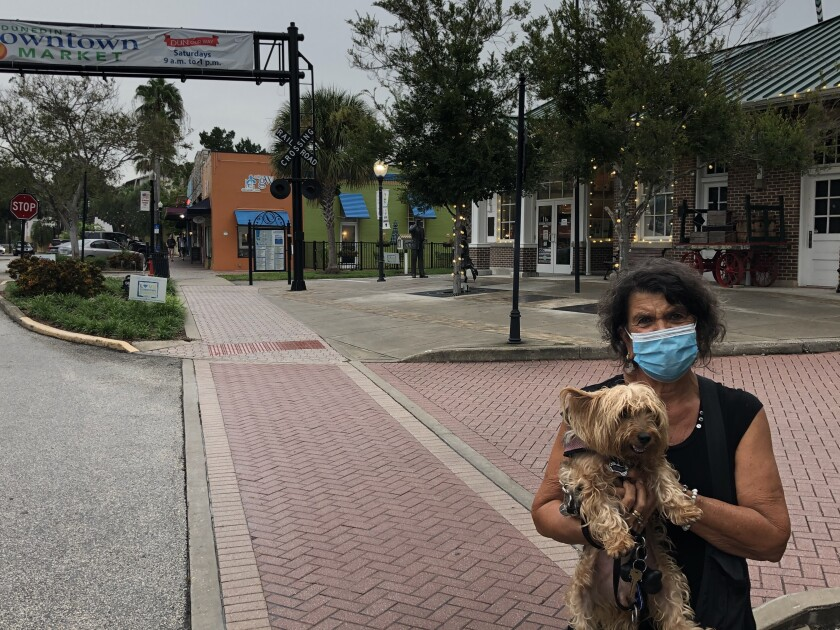 Melody Urso holds her dog, Rosie, as they pause while taking a walk in Dunedin, Fla.