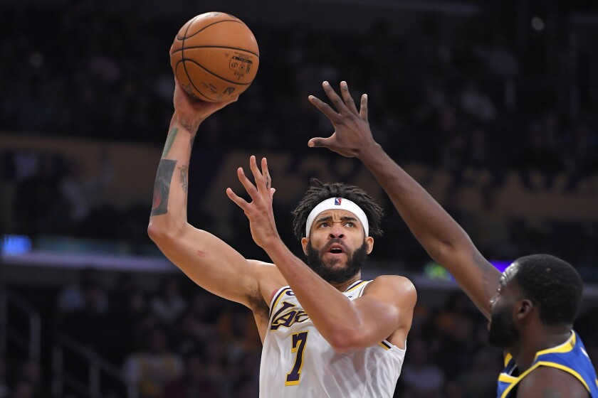 Lakers center JaVale McGee, left, shoots as Golden State Warriors forward Draymond Green defends during the first half of a preseason game on Wednesday at Staples Center.
