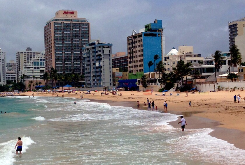 Beach-goers enjoy the surf in San Juan's Condado district, but experts say Puerto Rico's financial crisis is due in part to its failure to build up its tourist industry and capitalize on its Caribbean locale.