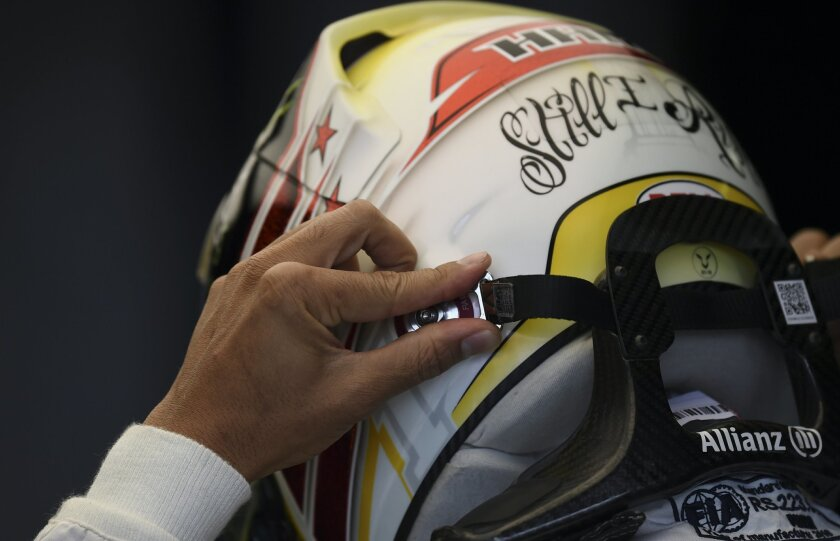 Mercedes driver Lewis Hamilton of Britain dons his helmet during the third practice session at the Australian Formula One Grand Prix at Albert Park in Melbourne, Australia, Saturday, March 19, 2016. The season's opening race will be held here on Sunday March 20. (AP Photo/Ross Land)