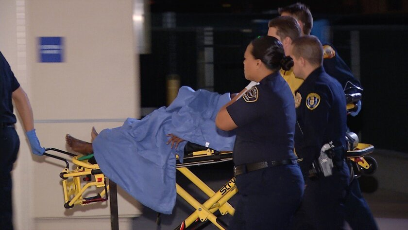 The suspect in a robbery who was wounded in a police shootout, identified as Ahmed Hassan Mumin, is wheeled away on a stretcher for treatment of a gunshot wound.