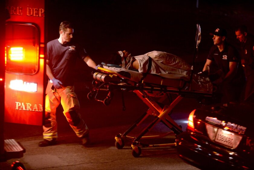 Paramedics transport one of the victims of a multiple shooting into an ambulance at Libby Lake in Oceanside on Wednesday.