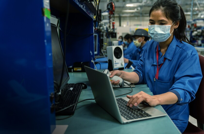 Workers test custom-built laptop computers that Qualcomm has donated to San Diego Unified School District.
