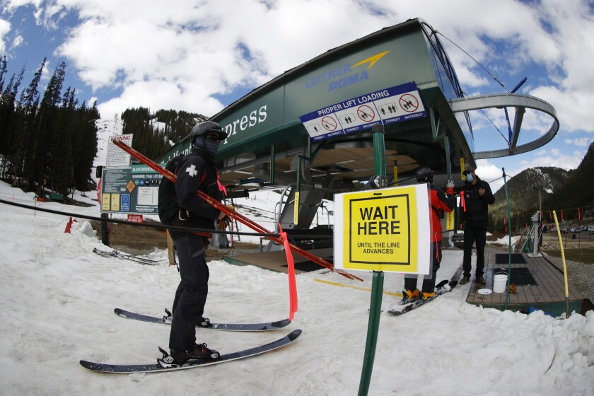 A lone member of the ski patrol waits to board a lift at the reopening of Arapahoe Basin Ski Resort, which closed in mid-March to help in the effort to stop the spread of the new coronavirus Wednesday, May 27, 2020, in Keystone, Colo. An executive order signed by President Donald Trump barring a wide variety of foreign visas has created another hurdle for ski resorts as they struggle to hire enough temporary workers to fill crucial jobs. (AP Photo/David Zalubowski, File)