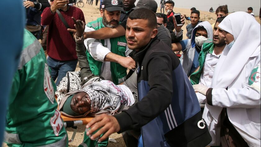 Palestinian paramedics carry away a woman who was injured during clashes with Israeli forces on the border between the Gaza Strip and Israel.