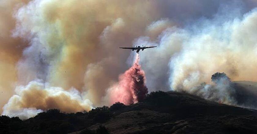 A plane drops fire retardant near the 91 Freeway in Anaheim Hills.