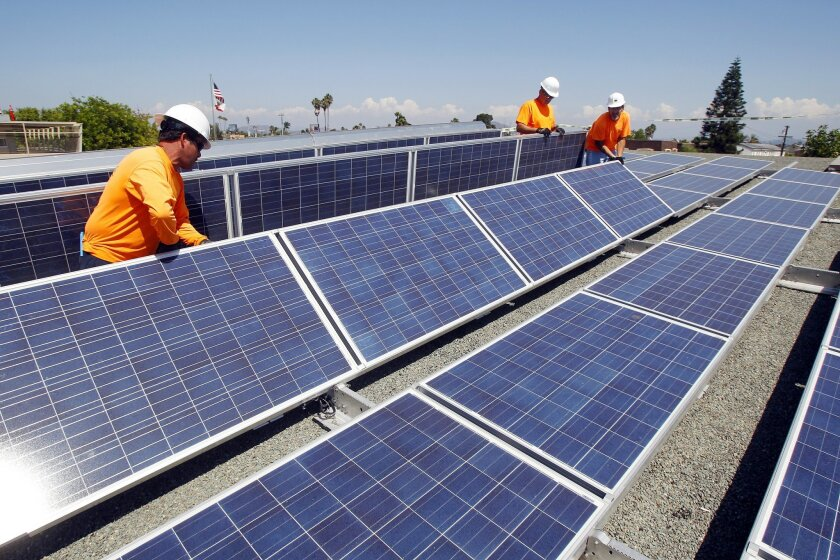 Work crews install solar panels on the roof of Adams Elementary School on Wednesday in San Diego in September.