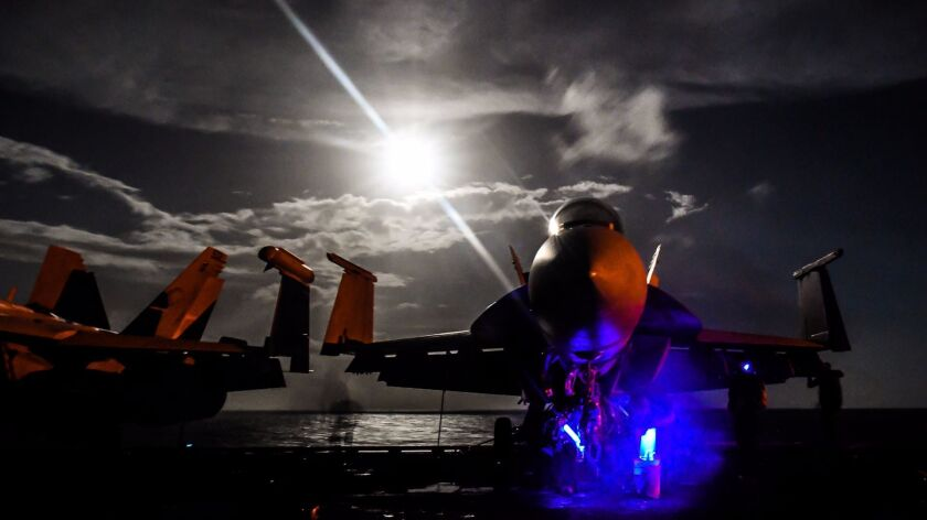 """Sailors on the flight deck of the carrier Theodore Roosevelt on Saturday inspect an F/A-18F Super Hornet assigned to the Lemoore-based """"Fighting Redcocks"""" of Strike Fighter Attack Squadron VFA-22."""