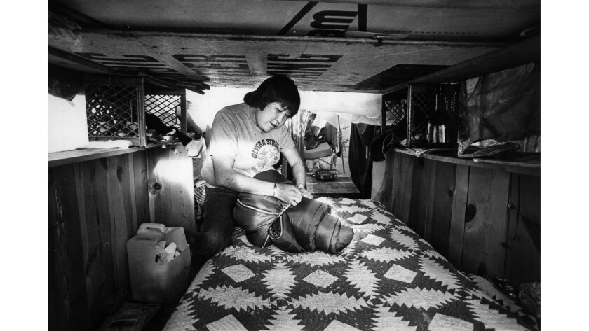 Feb. 5, 1984: Wilma Aros ties up bedrolls after making up bed inside makeshift shelter on Bunker Hil