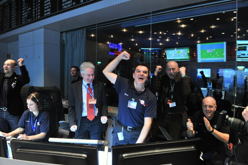 European Space Agency technicians celebrate after receiving a signal from the Rosetta spacecraft that it had emerged from a nearly three-year sleep to resume its comet-tracking mission.