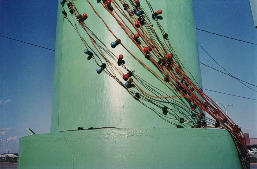 In this brightly hued shot by celebrated lensman William Eggleston, a strand of Christmas lights hangs on a jade-colored pole. It is Christmas without being Christmas.