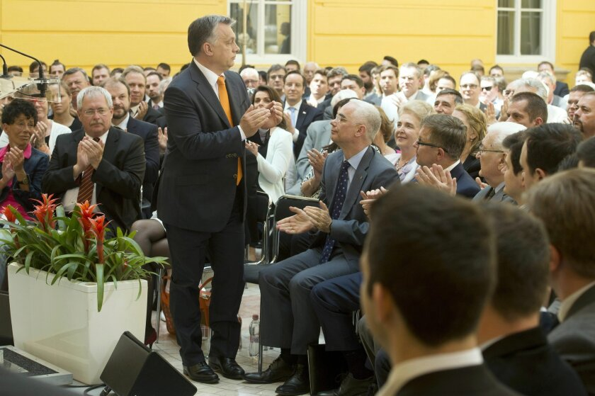 """Hungarian Prime Minister Viktor Orban, center, applauds the audience after he addressed a conference held on the occasion of the 5th anniversary of the formation of his government in 2010 in the atrium of the Budapest History Museum in Budapest, Hungary, Friday, May 29, 2015. Orban has recognized the far-right Jobbik party as the """"leading opposition party"""" and reaffirmed the country's commitment to its membership in the European Union and NATO. (Szilard Koszticsak/MTI via AP)"""