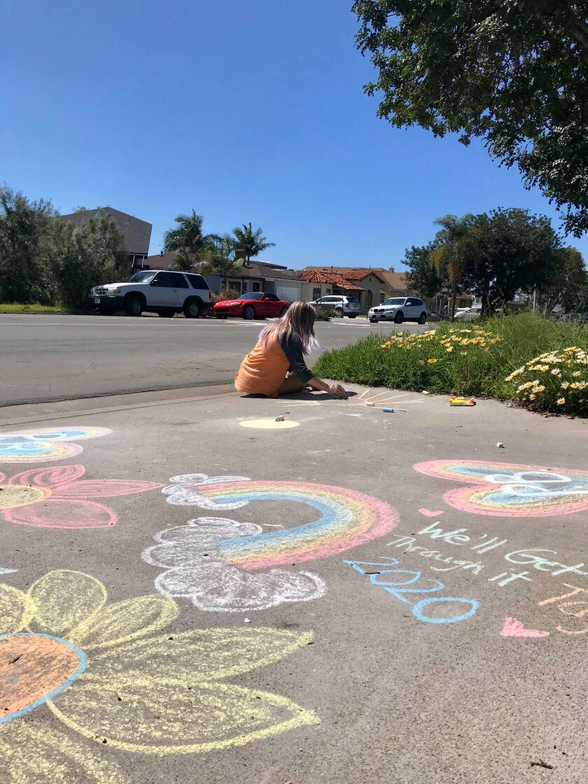 Avery Guyader, 11, beautifies the driveway of her family's Pacific Beach home during a Chalk the Walk event last weekend.