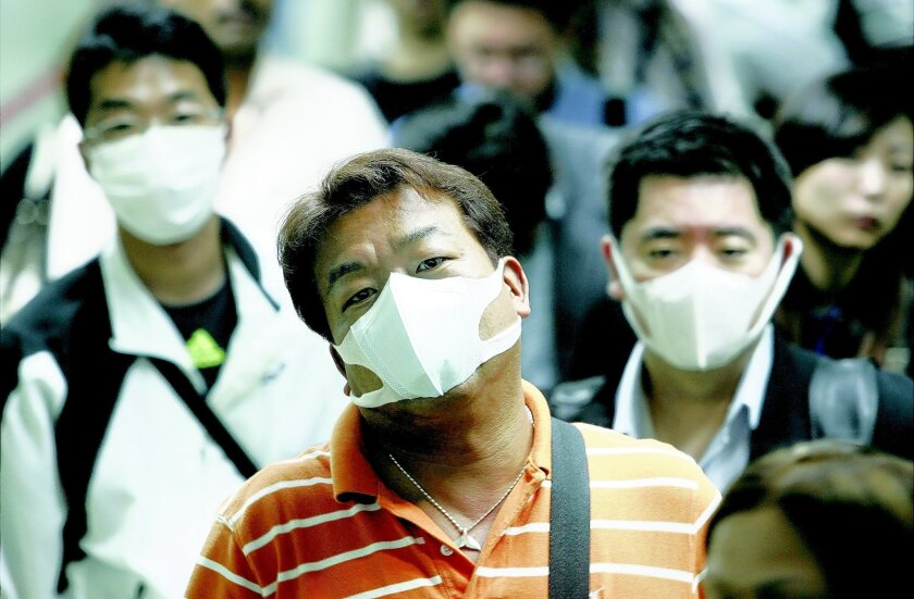 In 2009, travelers in the airport in Manila, Philippines, wore face masks for protection against the H1N1 virus. AP file Photo