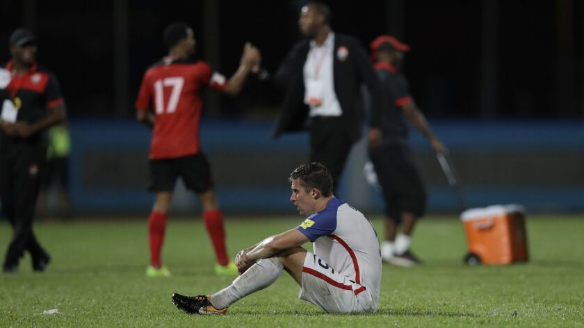 United States' Matt Besler, squats on the pitch after losing 2-1 against Trinidad and Tobago during