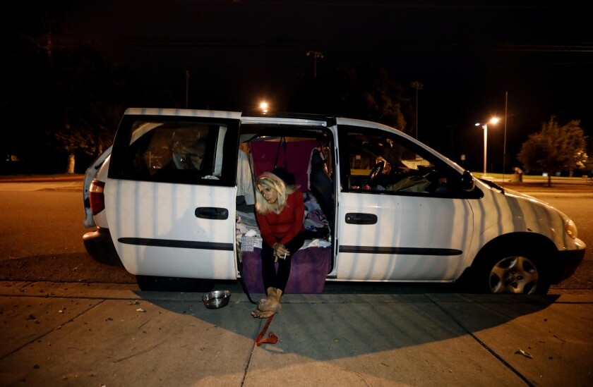 In the San Gabriel Valley, 70-year-old Andrea Colucci sits in the doorway of the van she and her dog are living in.