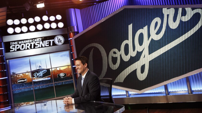 SportsNet LA anchor John Hartung sits in the television station's main studio in El Segundo. Time Warner Cable and the Dodgers are pushing for an arbitrator to determine a fair distribution price for the channel.