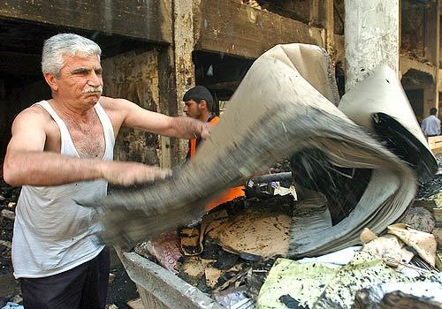 Abdul Adheem cleans up after the car bomb in Baghdad's historic booksellers district that killed more than 30 people.