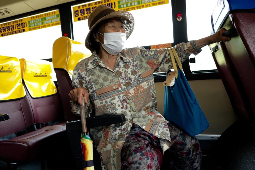 A woman holds on to an umbrella handle while sitting on the bus