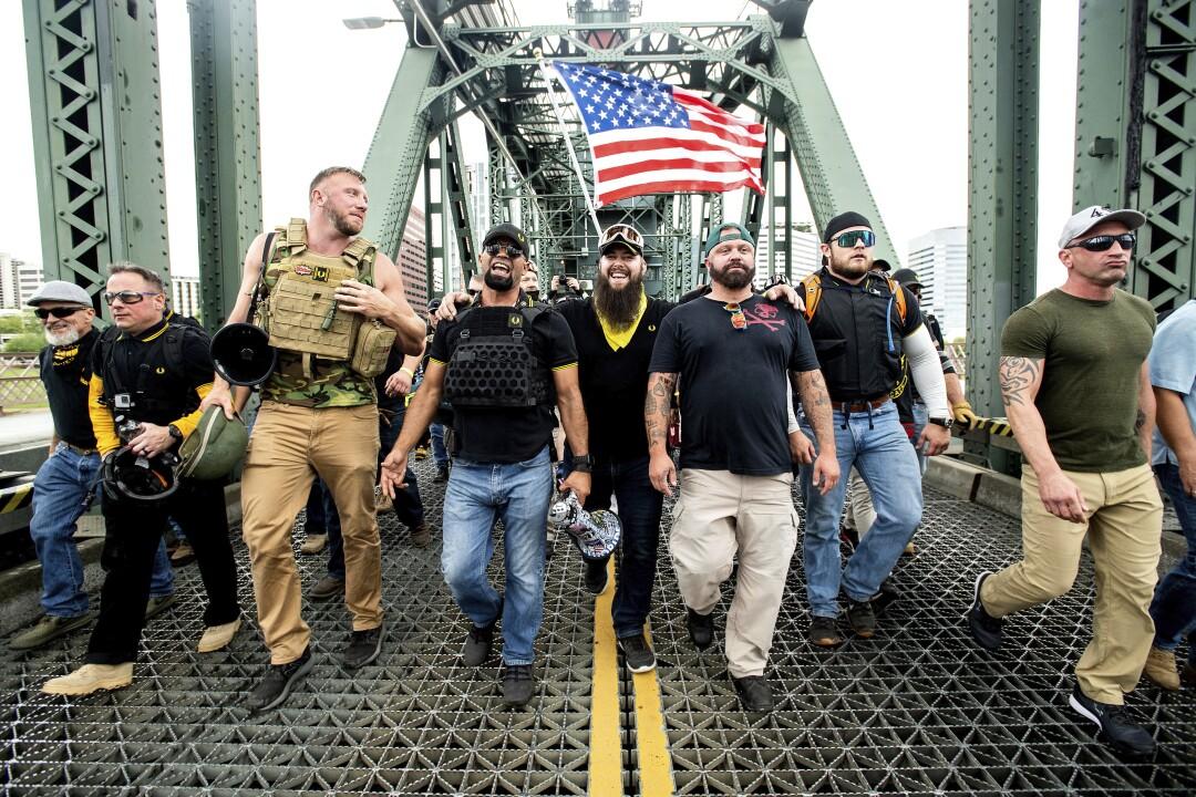 Men in tactical vests walk across a bridge