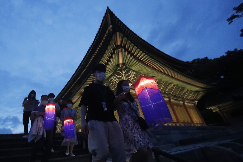 Visitors holding Korean traditional lanterns walk around during the Moonlight Tour at Changdeokgung Palace in Seoul, South Korea, Thursday, Aug. 13, 2020. The palace reopened Thursday after having been closed for two months due to the coronavirus pandemic. (AP Photo/Ahn Young-joon)
