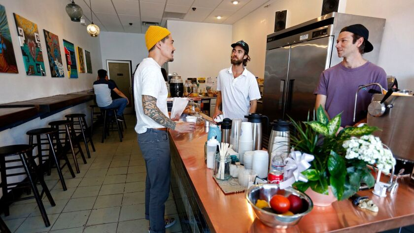 John Schwarz, center, and Jackson Defa, right, serve customers at Weird Wave Coffee.