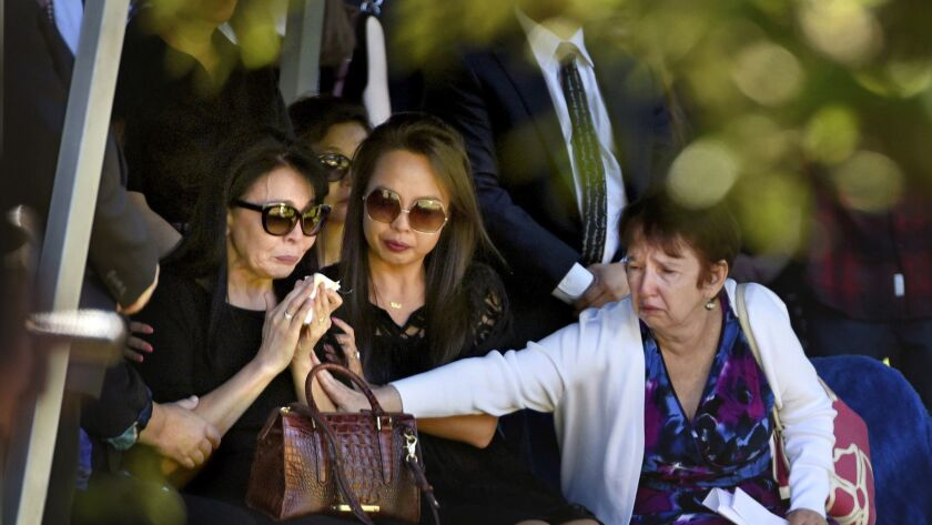 Erica Fischman, left, widow of Capital editor Gerald Fischman, is comforted by her daughter Uka Saran, center, and a relative during the gravesite service for Fischman on Sunday.