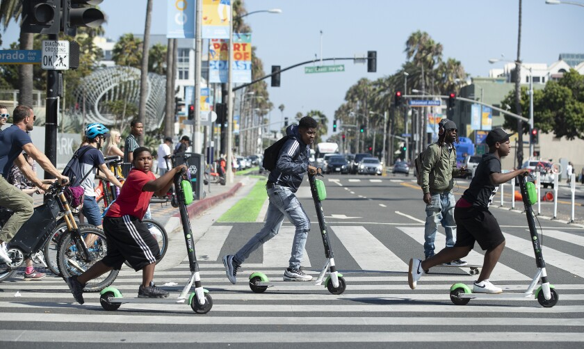People riding Lime scooters in a crosswalk in Santa Monica