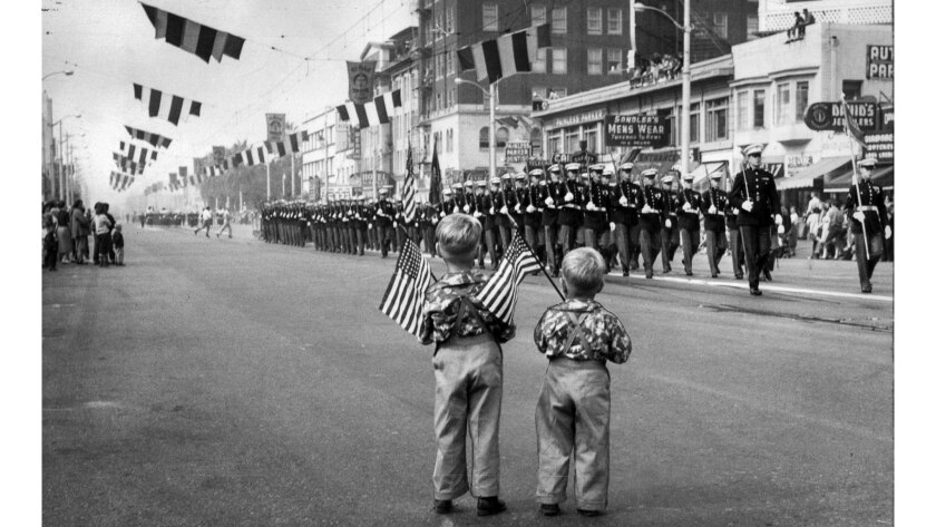 Nov. 11, 1952: Brother Scott, 4, and Billy, 2, Morris hold their flags and stand at attention as mar