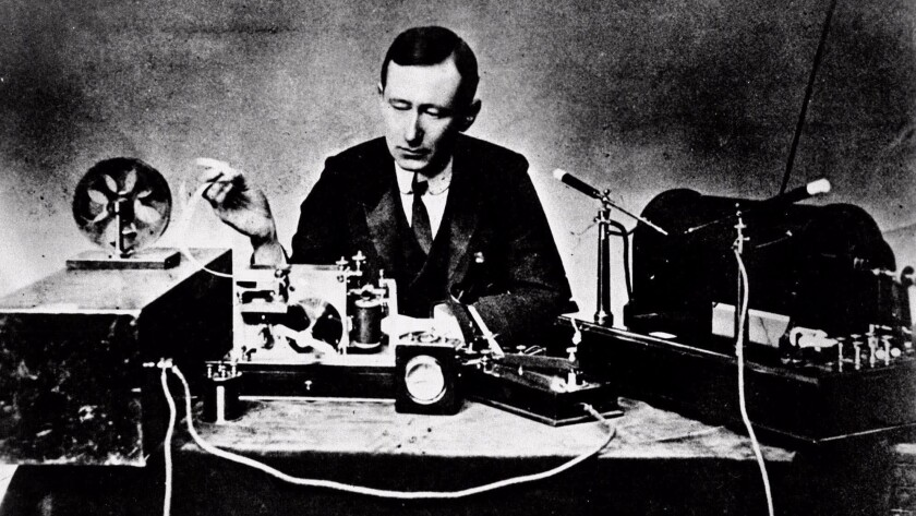 Italian physicist Guglielmo Marconi, the self-proclaimed inventor of radio, reads signals on a tape recorder, left, with a 10–inch spark coil used for ship–to–shore radio tests in this 1901 photo.