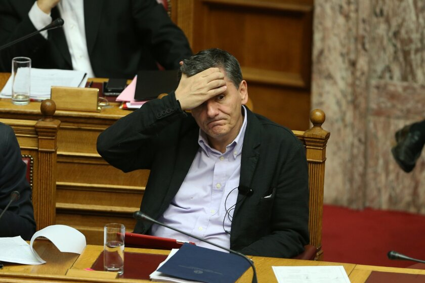 Greek Finance Minister Euclid Tsakalotos gestures during a parliamentary session for a reform bill vote, in Athens, Thursday, Nov. 19, 2015. Dissenters increased pressure on Greece's grudgingly pro-reform governing coalition Thursday, hours before an important vote on measures demanded by bailout creditors. (AP Photo/Petros Giannakouris)